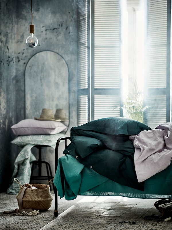 A bright bedroom with a bed made with green bed linen. Beside is a mirror and a stool holding extra pillows.