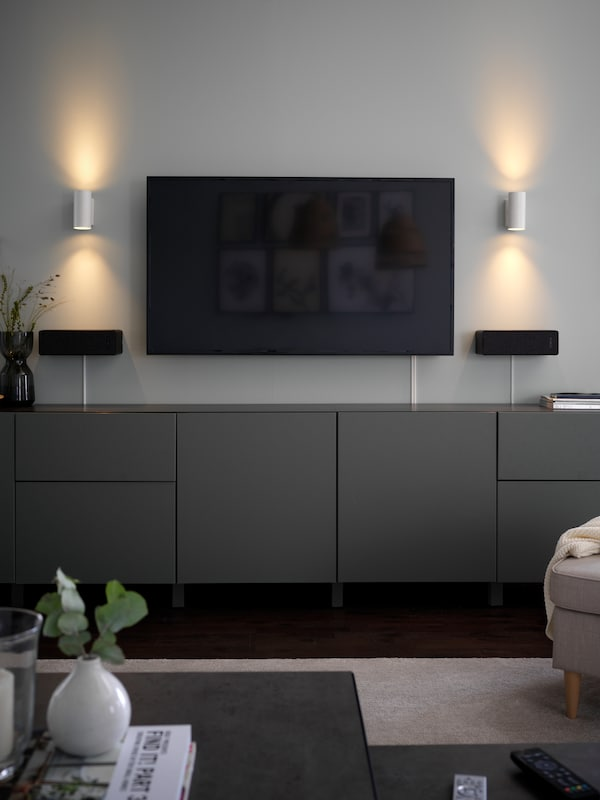 A pair of NYMÅNE wall up/downlighter lamps, one on either side of a wall-mounted TV screen above BESTÅ storage units.