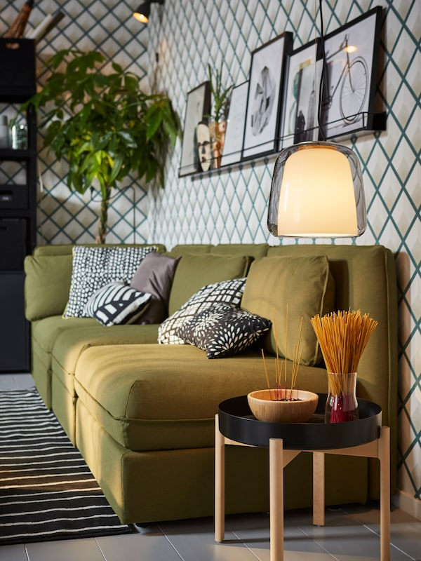 IKEA VALLENTUNA green modular sofa bed with storage, YPPERLIG birch and black coffee table and glass pendant lamp.