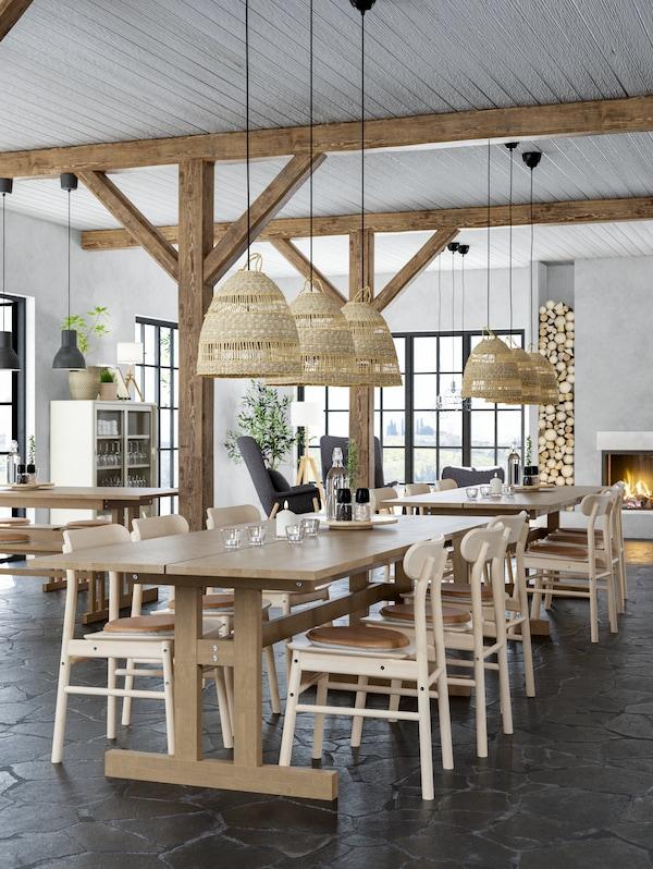 مطعم مصمم على طراز النزل مع طاولات خشبية طويلة وكراسي خشبية وعوارض خشبية مكشوفةومدفأة.