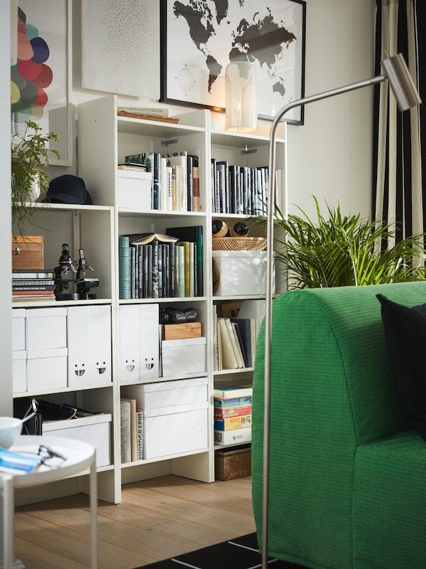 Hvide reoler, bøger, hvide opbevaringsbokse med låg, hvide tidsskriftssamlere, potteplanter og kunst på væggen.