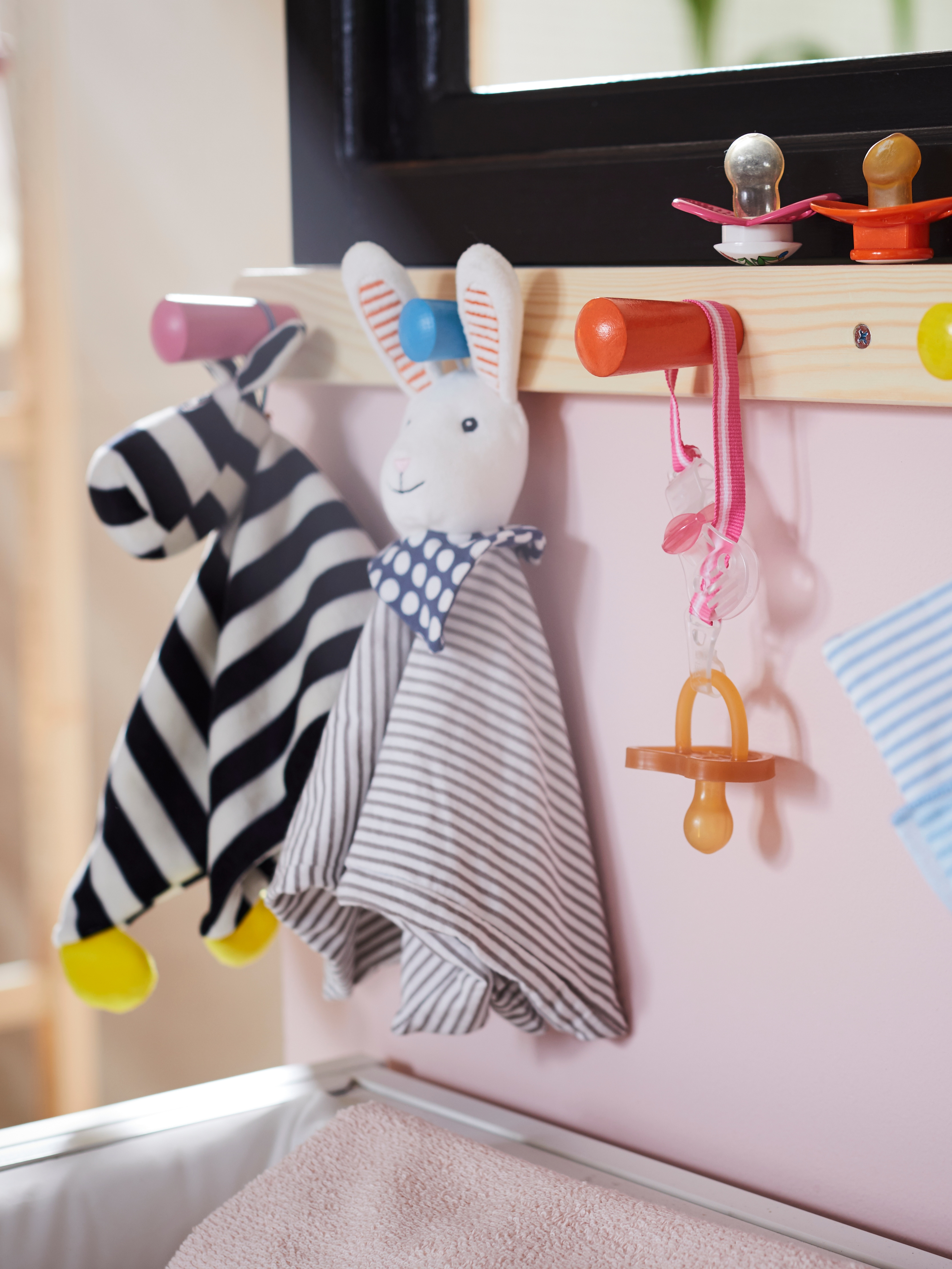 A FLISAT rack with four brightly coloured knobs on a pink wall, holding two KLAPPA comfort blankets and a soother.