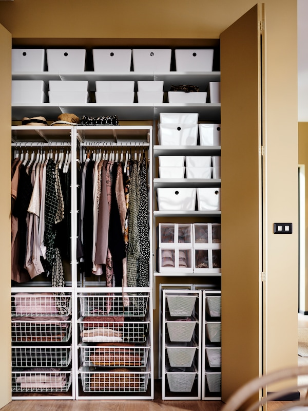 The door of a light-brown fitted wardrobe is open to show JONAXEL system frames, shelves and baskets with clothes hanging.