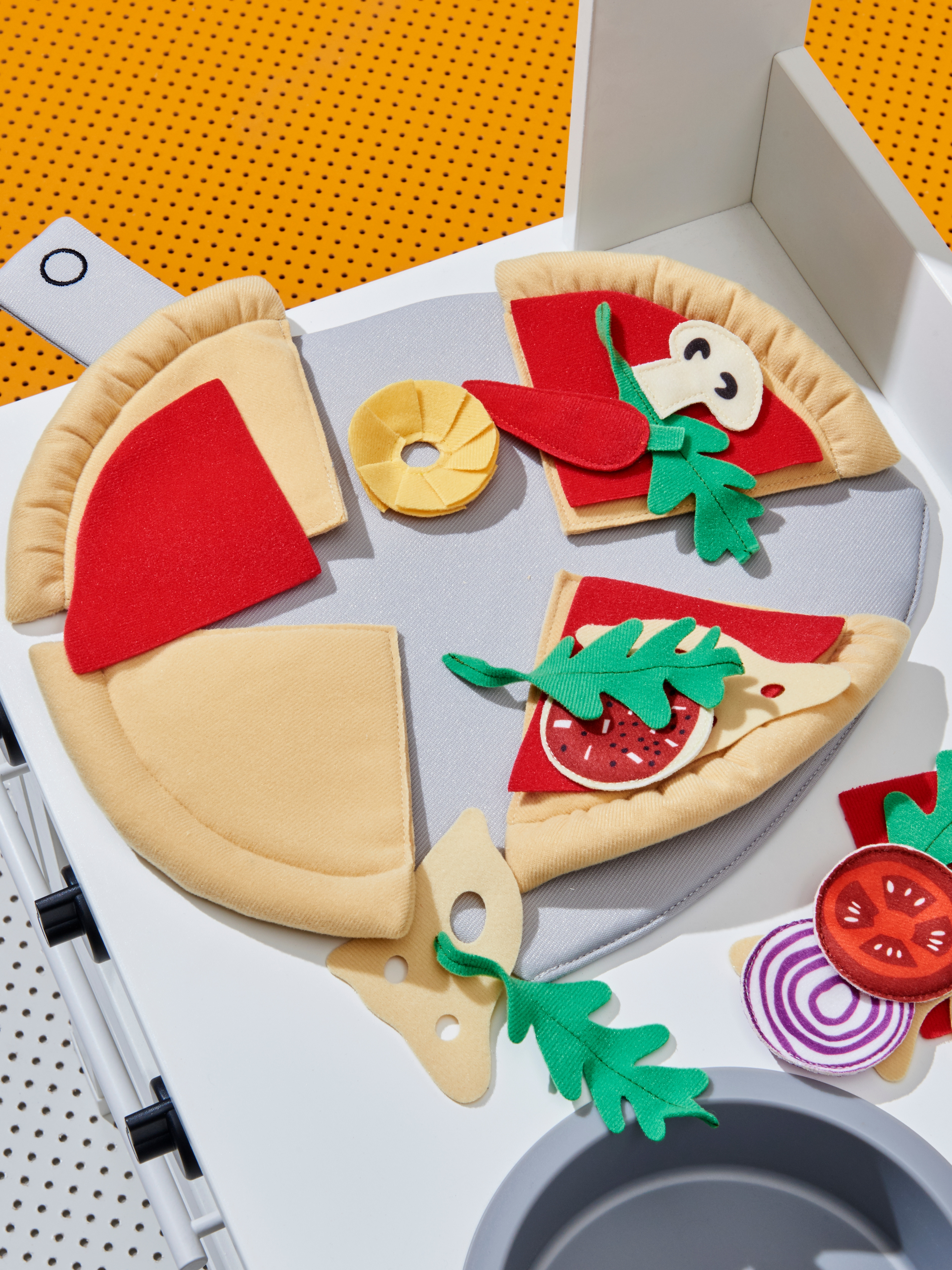 Close-up of soft fabric DUKTIG pizza toy with multi-coloured toppings on a white children's toy oven.