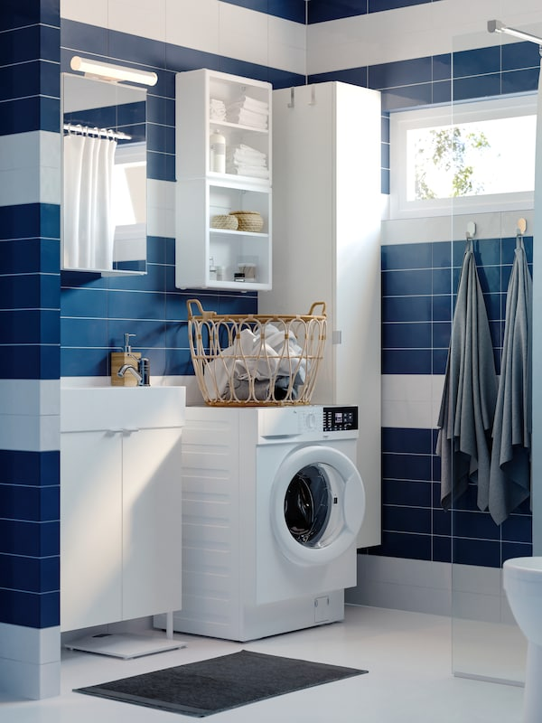 A blue/white bathroom with a white wash-basin cabinet with 2 doors, a mirror cabinet, and a white open storage shelf unit.