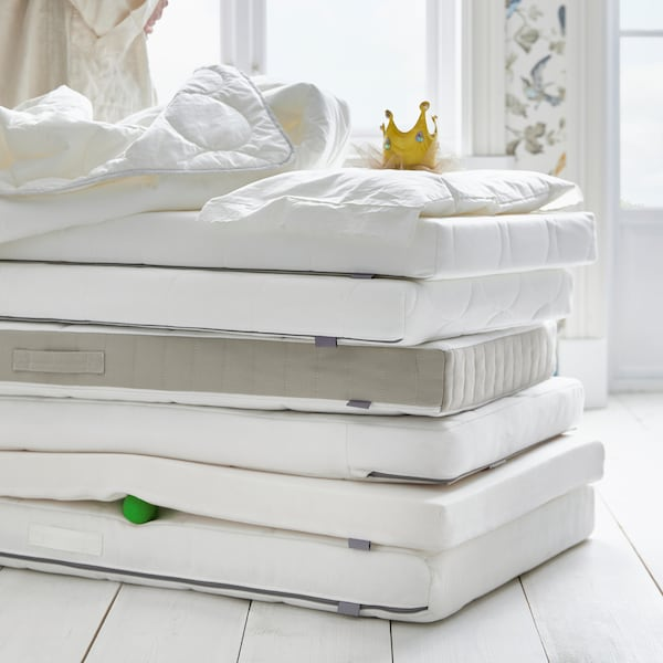 A lot of crib mattresses are stacked on top of each other on a floor with a duvet, a pillow and a toy crown on top.