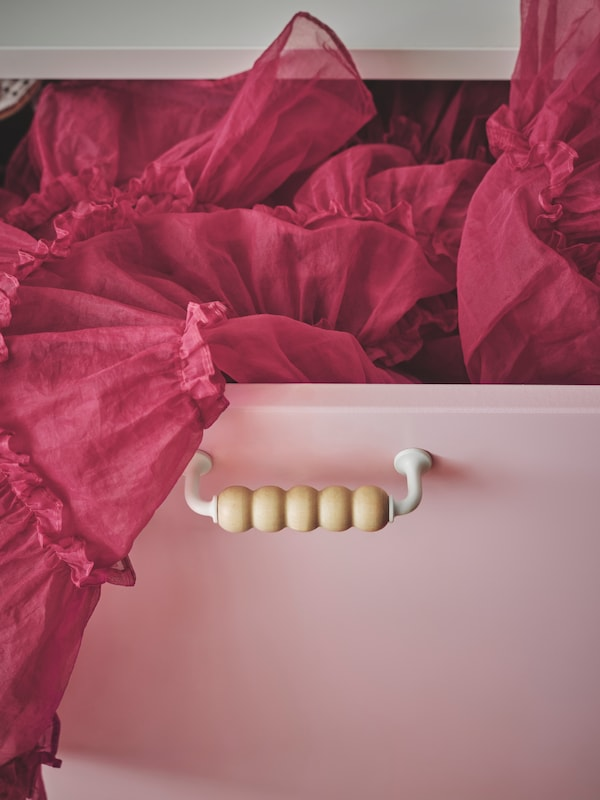 SMÅSTAD skuff med rosa front og LAPPMES håndtak i tre er delvis åpen, og et mørkerosa ballerinaskjørt stikker ut av den.