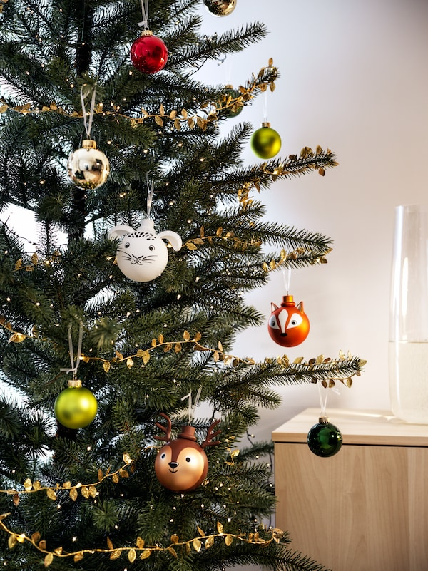 A tree is decorated with ornaments in a living room. An open box of baubles and other boxes are under the tree.