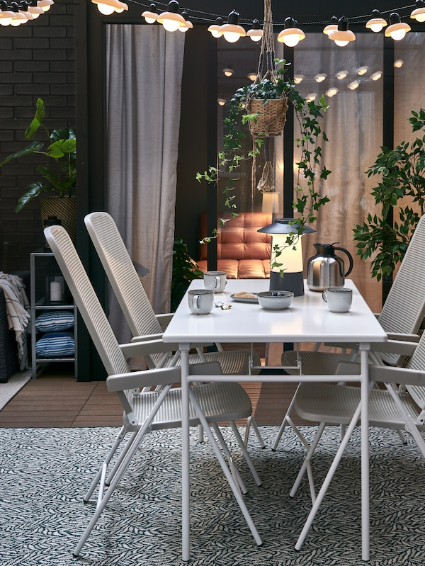 베이지/그린 러그 위에 화이트 테이블과 화이트/베이지 접이식 메시 의자를 놓은 해질 무렵의 파티오.