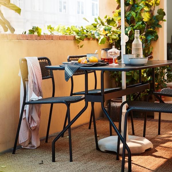 Ein dunkelgraues Essmöbel-Set auf einem Balkon. Auf dem Tisch sind Obst, Tee, Wasser und Geschirr zu sehen.