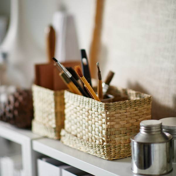 LURPASSA boxes containing paint brushes and other small items placed on a white shelf next to small silver containers.