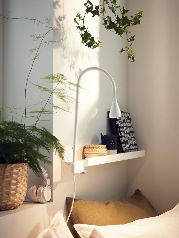 Sur le mur, une étagère pour photos blanche utilisée comme table de chevet, accueillant une liseuse, un réveil et des livres.