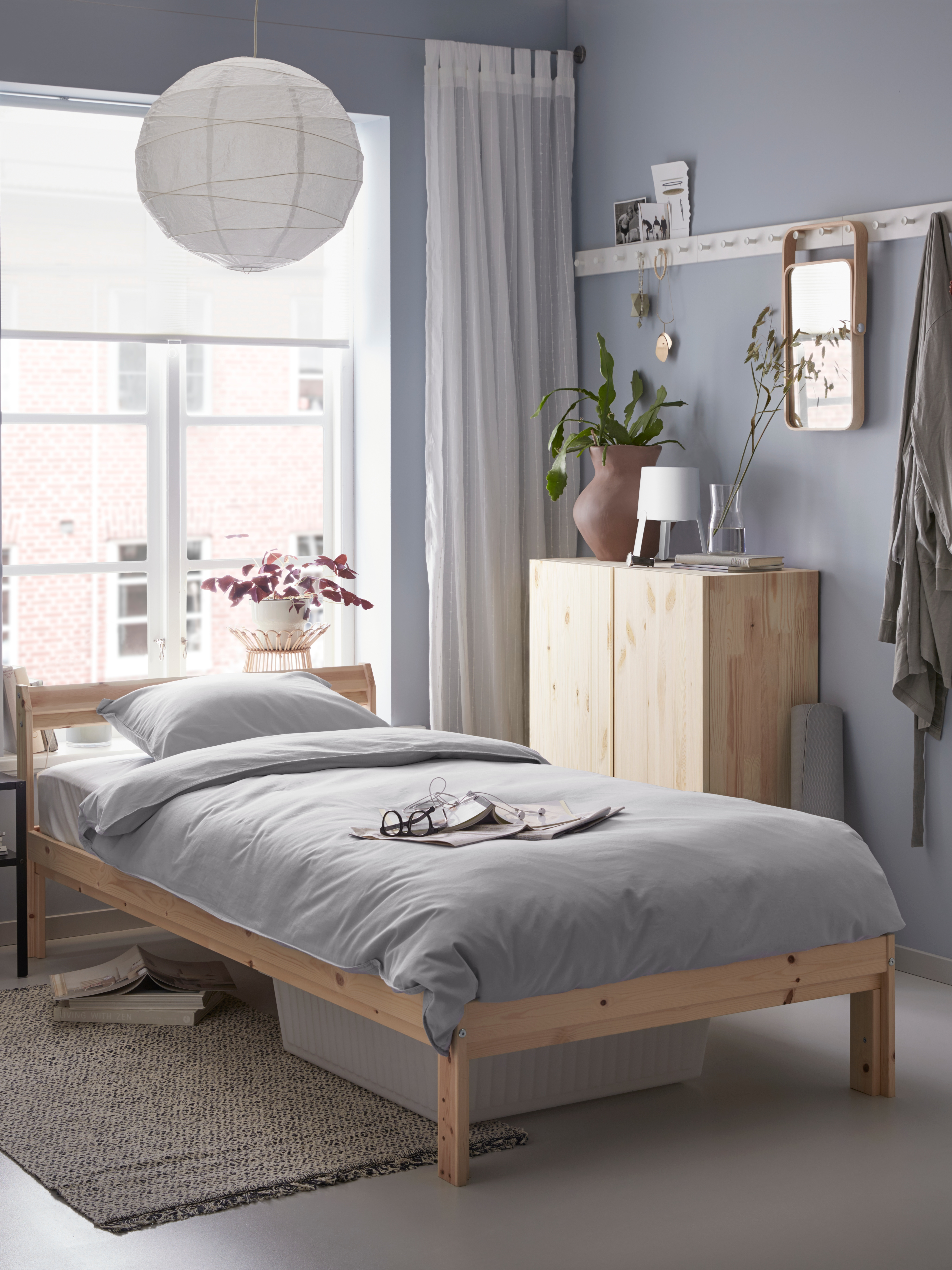 NEIDEN pine bed frame, with grey quilt cover and pillowcases, by a window in a grey-scaled bedroom next to a pine cabinet.