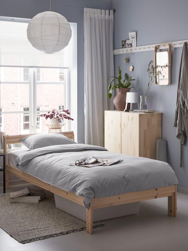 Sovrum med möbler i furu och ljust gråa väggar.