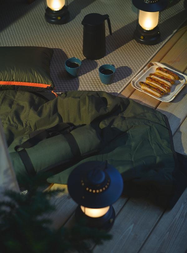 STORHAGA led-lantaarns verlichten 's avonds een kampeerpicknick op het terras, inclusief hotdogs en koffie.