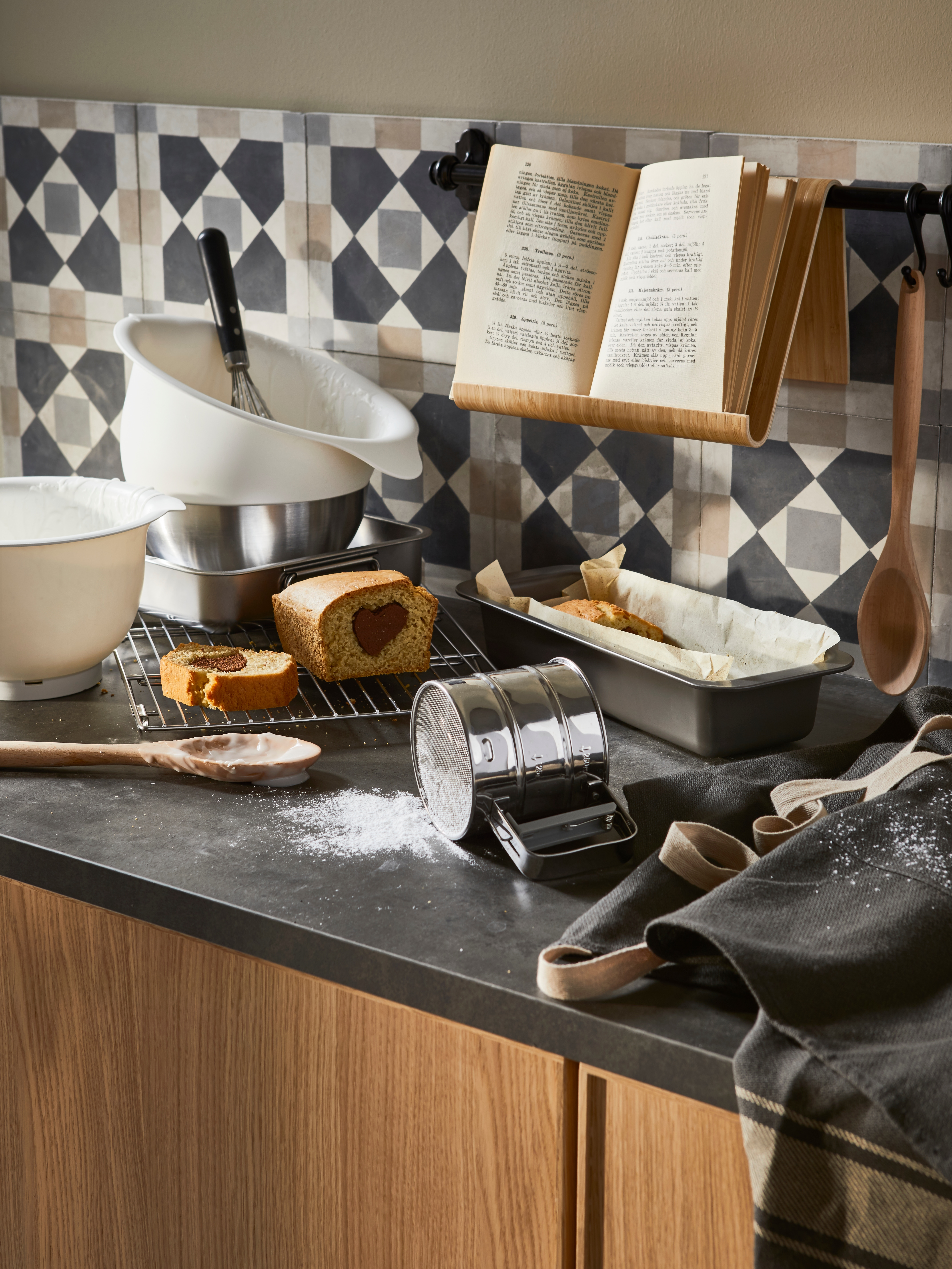 A worktop with HEMMABAK loaf tin, cake on a wire rack, stacked mixing bowls, apron, recipe book, utensils and spilt flour.