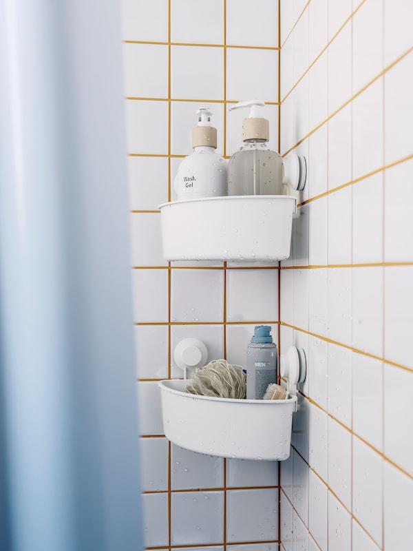 Dua unit rak penjuru berwarna putih dengan pelekap sedut yang diletakkan syampu dan botol gel mandian serta span mandian.