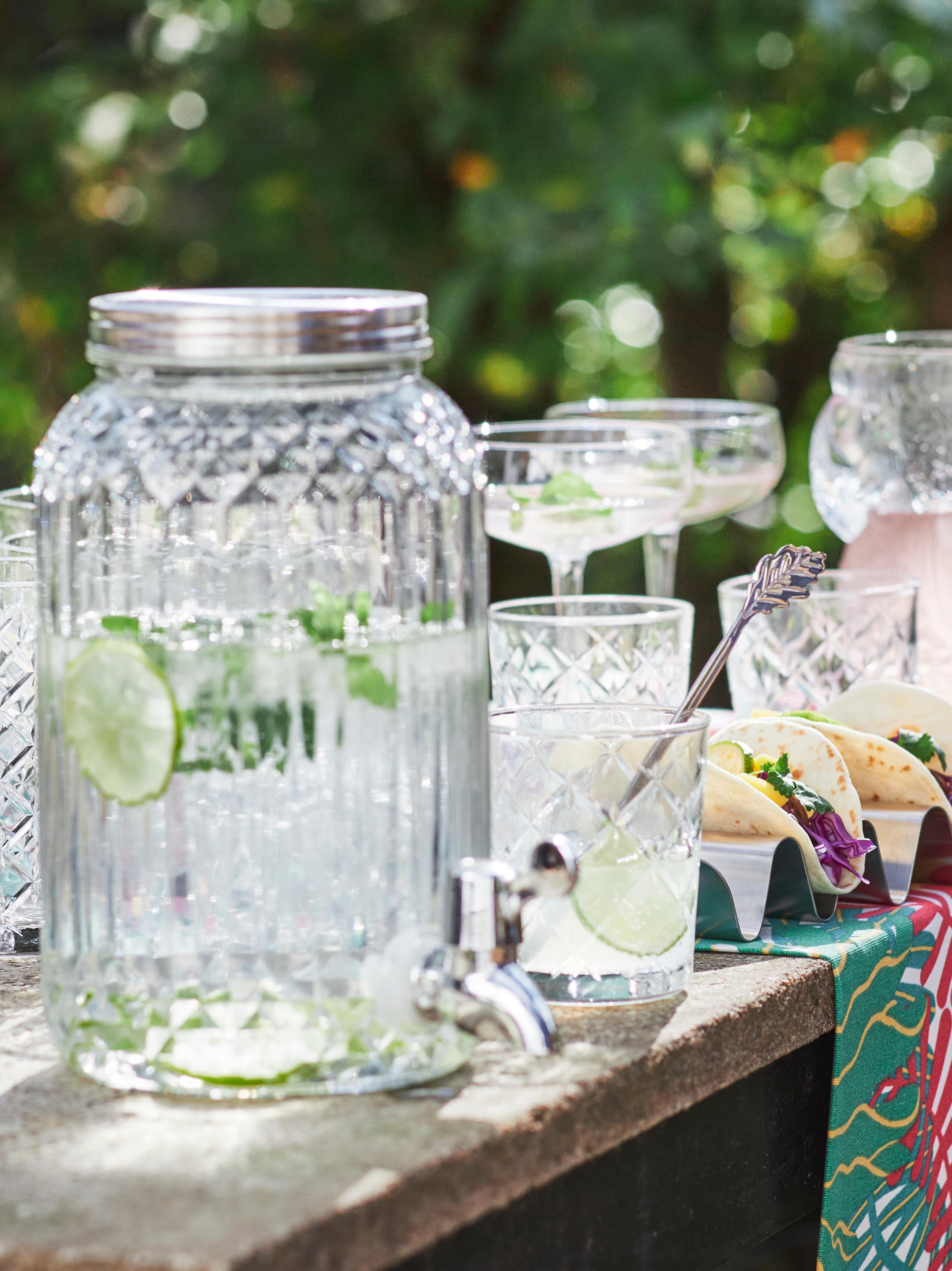 Des verres et un bocal en verre transparent KALASFINT avec un robinet contenant de l'eau et des tranches de citron vert posés sur une tablette en pierre utilisée comme table.