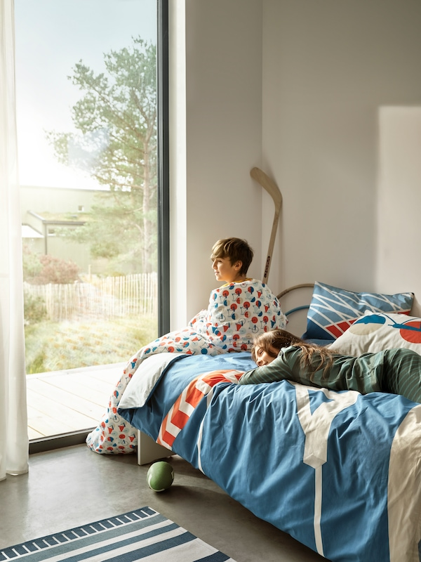 Una ragazza è distesa su un letto con biancheria SPORTSLIG ispirata alle piste di atletica. Un ragazzo è seduto sul letto con un piumino avvolto intorno alle spalle.