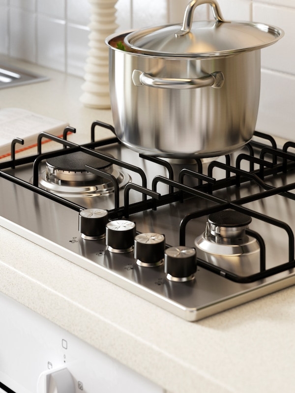 A silver pot on a hob in a kitchen with a white worktop next to a metal sink.