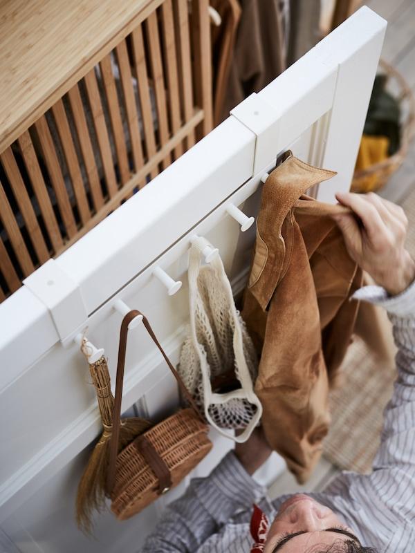 A hallway door with a white ENUDDEN hanger for door, a net bag, a rattan handbag and a man grabbing his jacket.