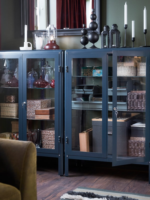 Two black-blue glass-door cabinets with decorative boxes inside and candles on their top surfaces. A mirror hangs above.