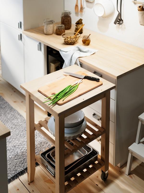 Na brezovom kuchynskom vozíku BEKVÄM je doska na krájanie, na nej zelené cibuľky a nôž, vozík stojí vedľa pracovnej dosky EKBACKEN.