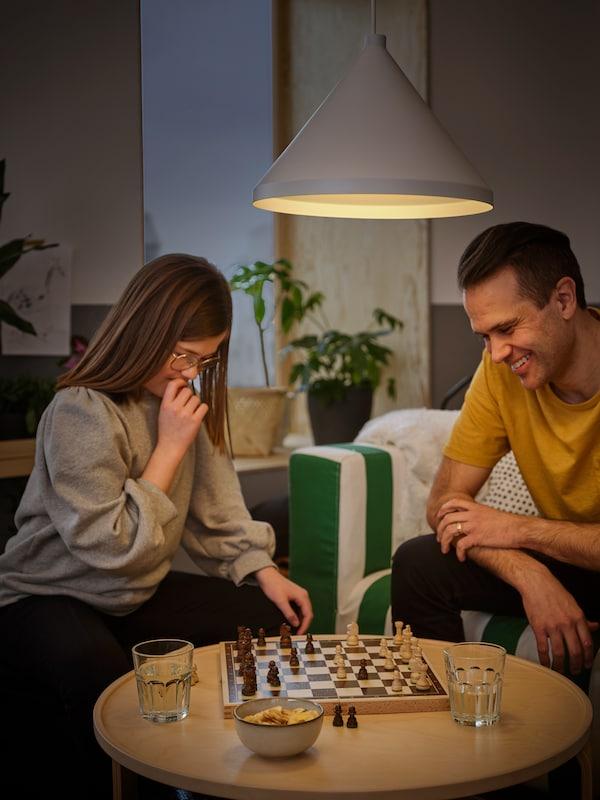 Dans un salon, une préadolescente et son père jouent aux échecs. Une suspension NÄVLINGE procure un éclairage en plongée au-dessus du jeu.