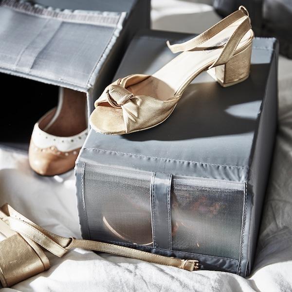 Deux boîtes à chaussures à mailles SKUBB gris foncé sur un lit avec des chaussures à l'intérieur et une sandale beige sur le dessus.