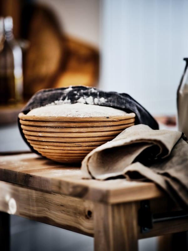 Une table en bois avec un banneton contenant de la pâte à pain, à moitié couverte par un torchon à vaisselle.