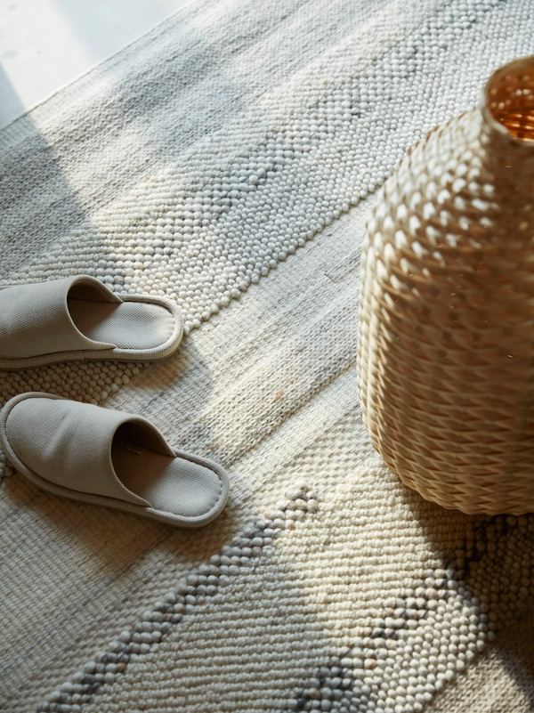 A hand-woven rug in white with a unique design, a pair of light grey slippers and a seagrass vase stand on it.