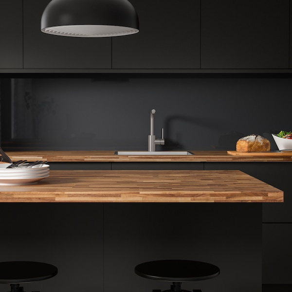A kitchen island with PINNARP worktop in walnut veneer and a matching worktop with a sink in the background.