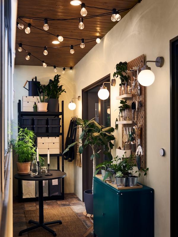 خزانة خضراء وطاولة سوداء ووحدة رفوف BROR، مع مصابيح حائط FRIHULT وسلاسل إضاءة وأضواء سقف موجهة.