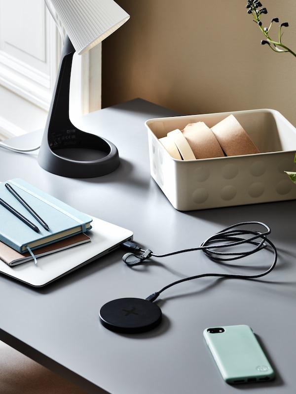 Sötétszürke-fehér SVALLET íróasztallámpa áll egy asztalon, egy telefon és egy laptoppal összekötött vezeték nélküli töltő mellett.
