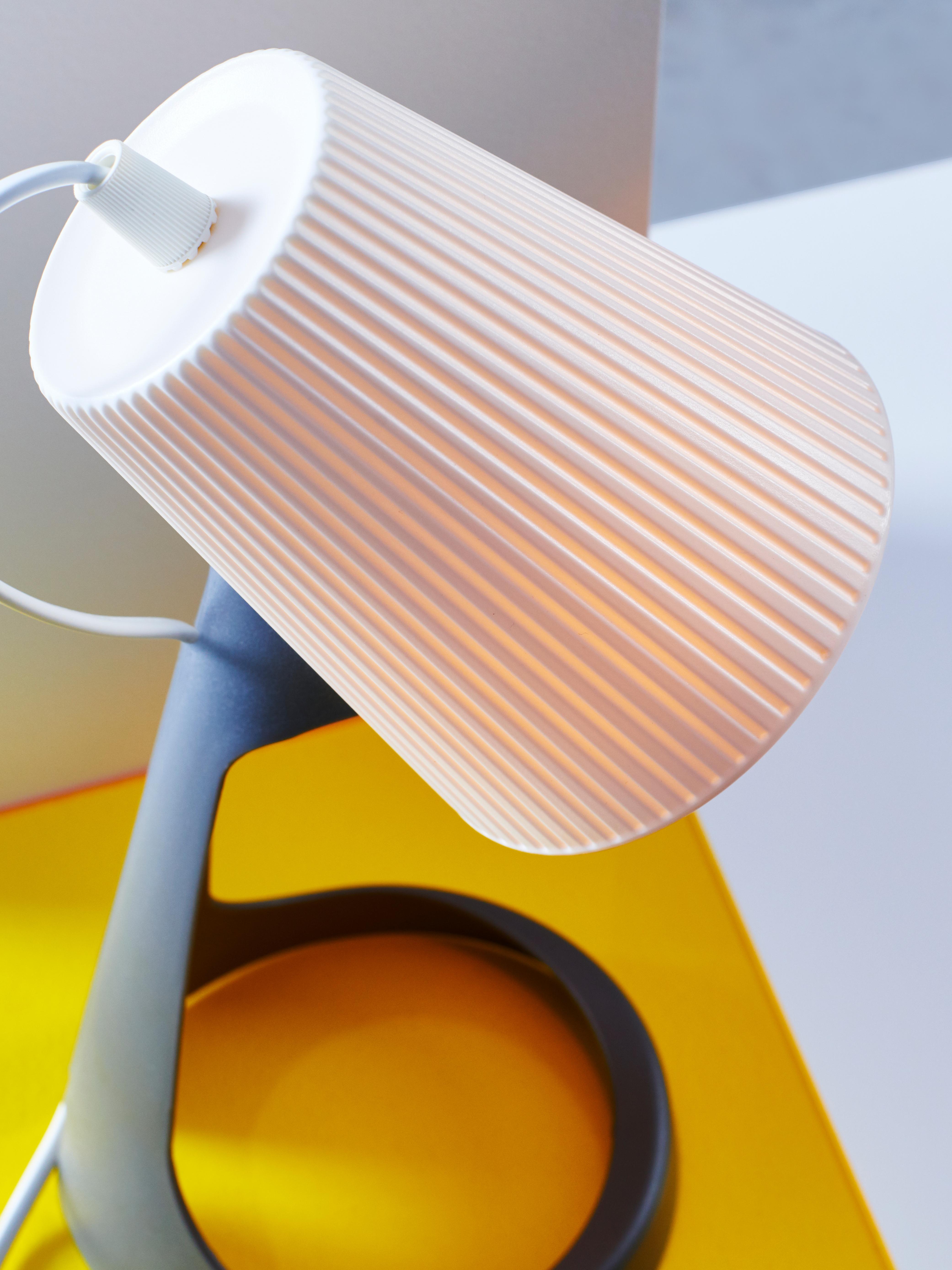 SVALLET radna lampa tamnosive i bijele boje na žutom postolju.