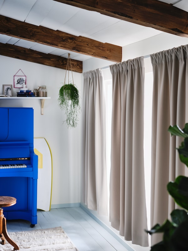 Egy kék zongora áll az ablakok mellett, melyeket világos szürke-bézs színű MAJGULL anyagból készült függönyök takarnak el félig.