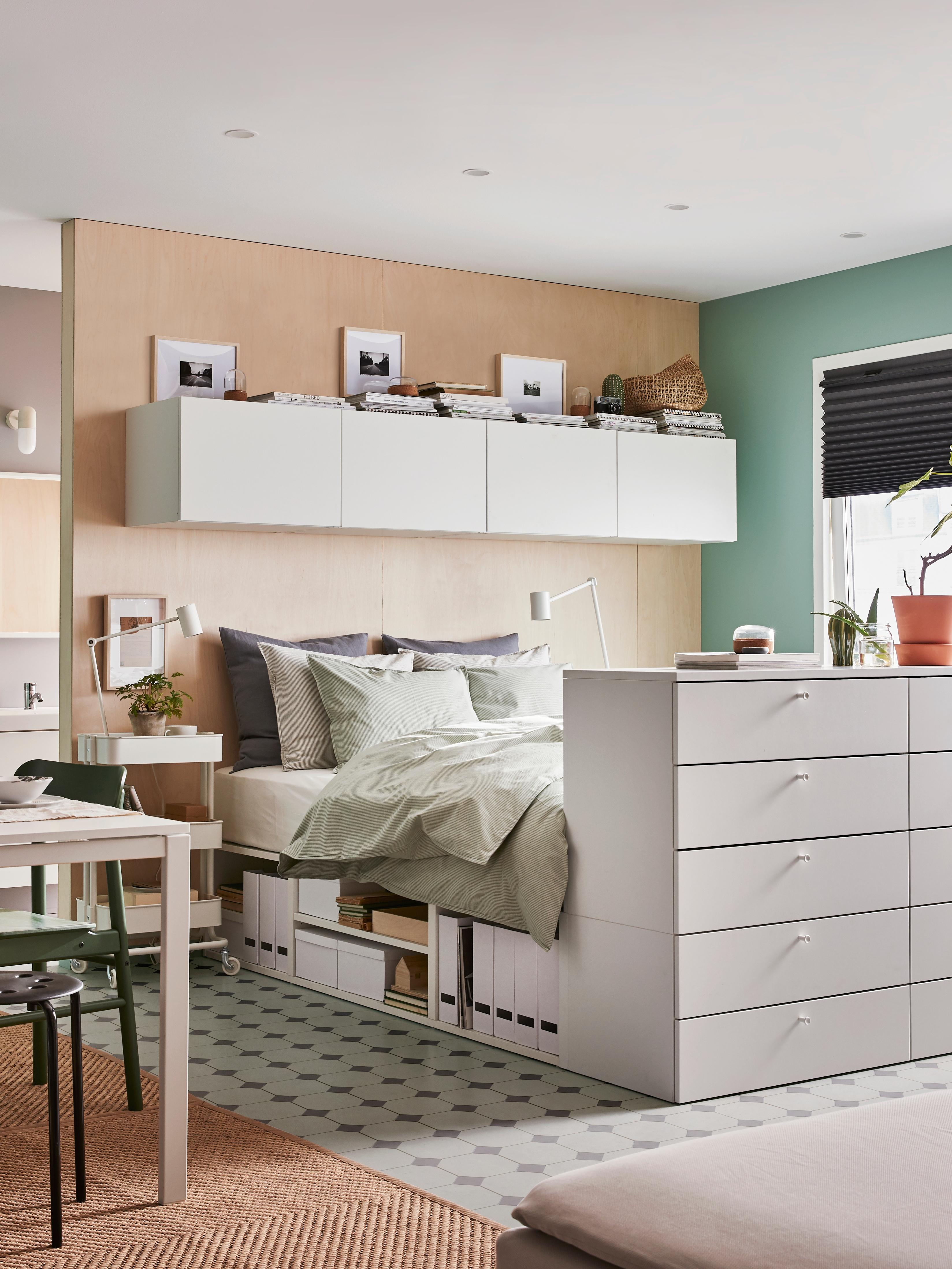 Cadre de lit PLATSA dans une chambre avec une table, sur un sol carrelé. Le lit est fait avec du linge de lit neutre et cache un espace de rangement en dessous.