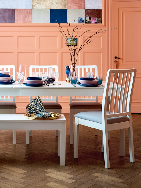 In an orange room: a white EKEDALEN table with matching chairs and bench, pink and blue tableware and a branch in a vase.