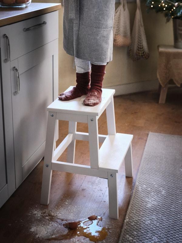 Dva stopala prekrivena bijelim brašnom stoje na BEKVÄM prenosivoj stepenici u kuhinji tradicionalnog stila s drvenim podovima.