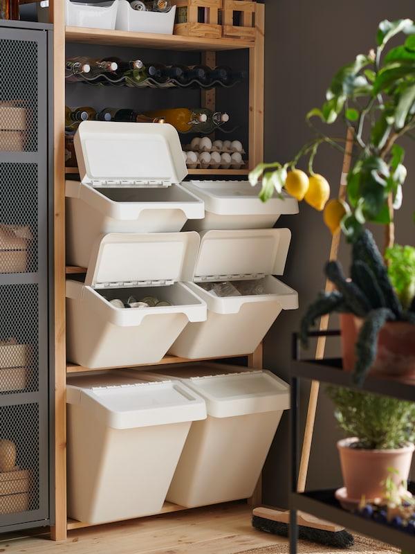 Le coin d'une pièce avec une étagère IVAR remplie de poubelles SORTERA blanches de différentes tailles sous un range-bouteilles.
