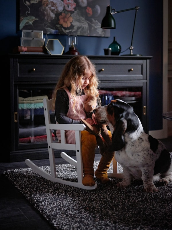 A child sits in a white SUNDVIK rocking chair placed on a VINDUM high pile rug, looking at a pet dog in front of her.