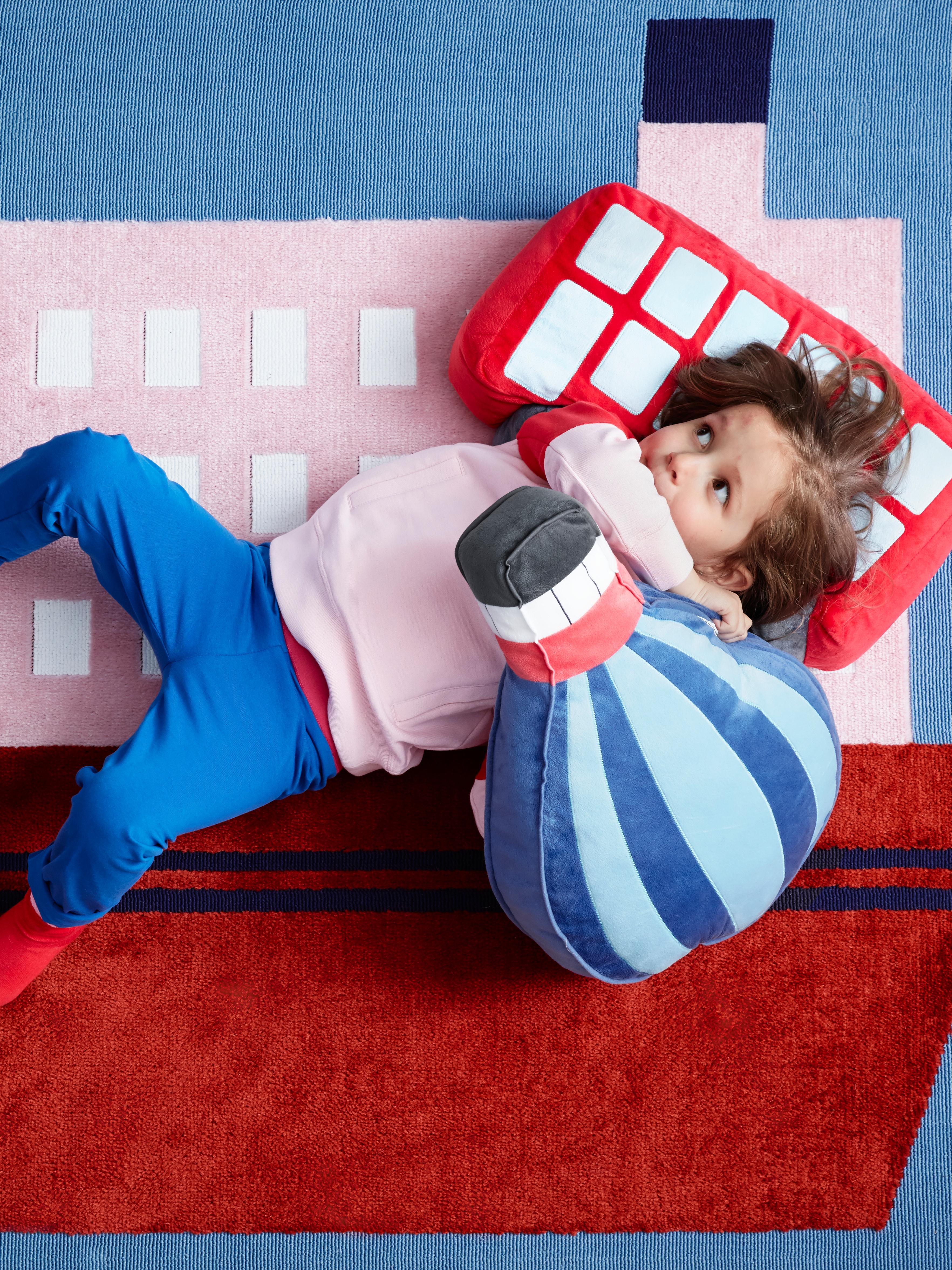 Neno tombado sobre unha alfombra UPPTÅG con debuxos de barcos sostendo unha almofada con forma de globo aerostático; a súa cabeza descansa sobre unha almofada de cor vermella.