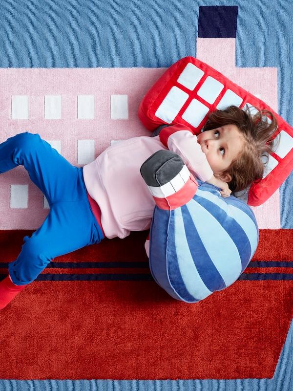Dijete leži na UPPTÅG tepihu s UPPTÅG ukrasnim jastukom u obliku autobusa i drugim u obliku balona na vrući zrak.