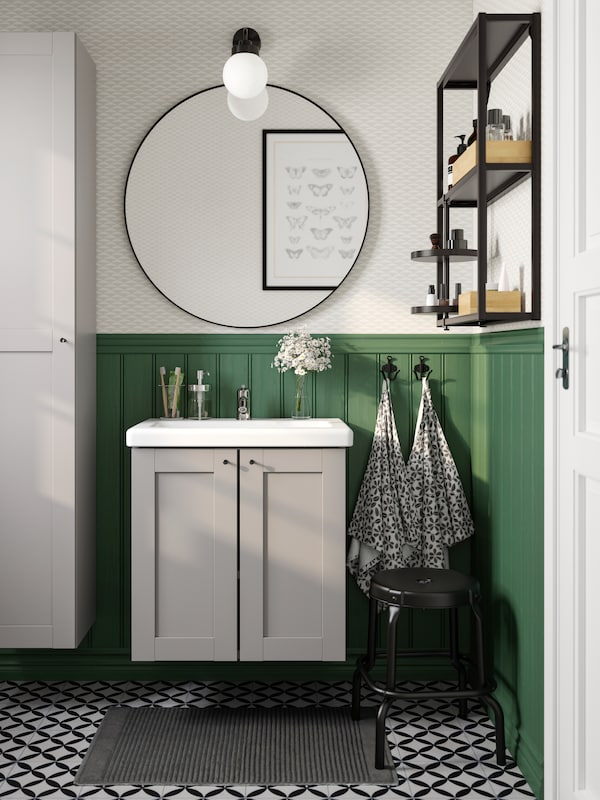 A big round black mirror hangs above a white wash-basin with two grey cabinet doors below it against a green wall panel.