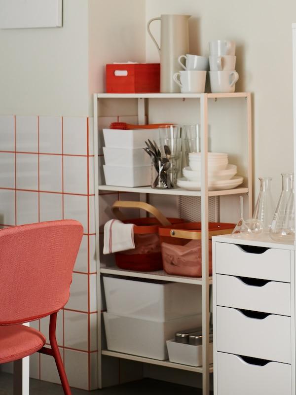 Ein offenes Regal in Weiss mit verschiedenen Küchenutensilien, Körben und Behältern neben einem weissen Schubladenelement.