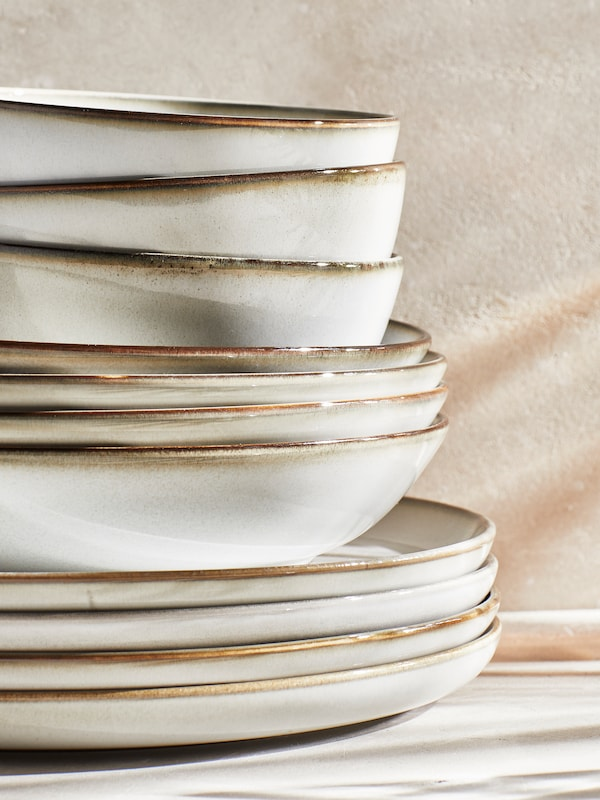 A pile of GLADELIG grey plates, deep plates and bowls stacked on top of each other.