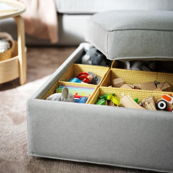 Un repose-pieds KIVIK gris clair avec un couvercle à moitié ouvert, révélant des jouets rangés dans plusieurs boîtes UPPRYMD jaunes.