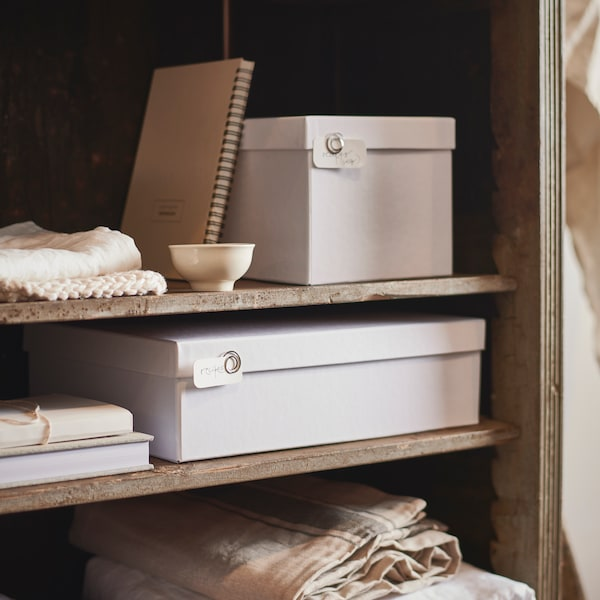 White TJENA storage boxes with lids, books, tablecloths and a small ceramic cup sit on shelves inside a cabinet.