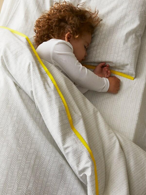 Un bambino dorme in un lettino con un set biancheria per lettino 3 pezzi KLÄMMIG in cotone proveniente da fonti più sostenibili - IKEA
