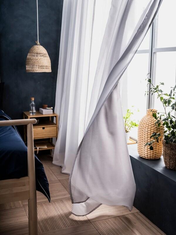 Eine GUNRID luftreinigende Gardine hängt nahe einer TORARED Hängeleuchte aus Seegras und einem NORDKISA Beistelltisch an einem Fenster.